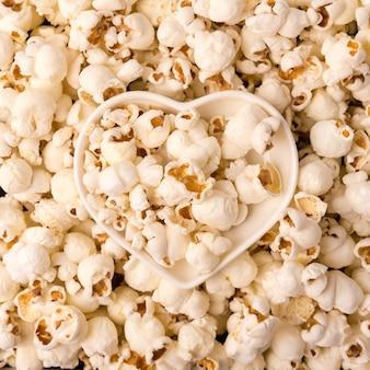 Домашний попкорн как подробный снимок крупным планом, чаша в форме сердца, вид сверху.