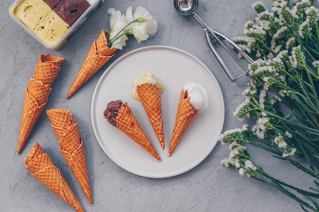 白、トップビューで花とプレートのいくつかのアイスクリーム。