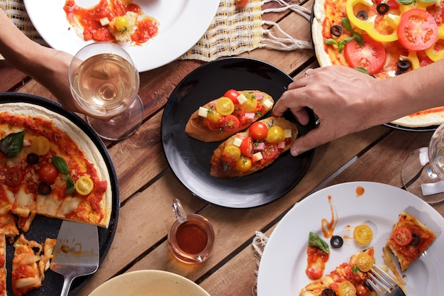 Some italian cuisine on wooden table with human hands