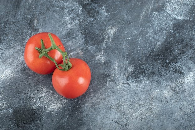 Some of juicy tomatoes on gray .