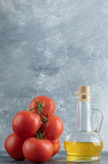 Some juicy tomatoes with a glass bottle of oil.