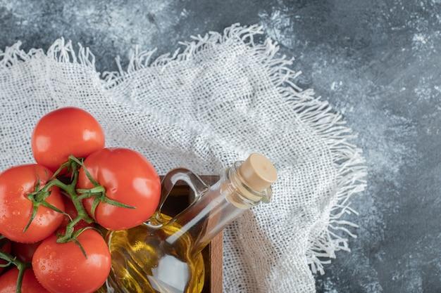Alcuni pomodori succosi con una bottiglia di vetro di olio.