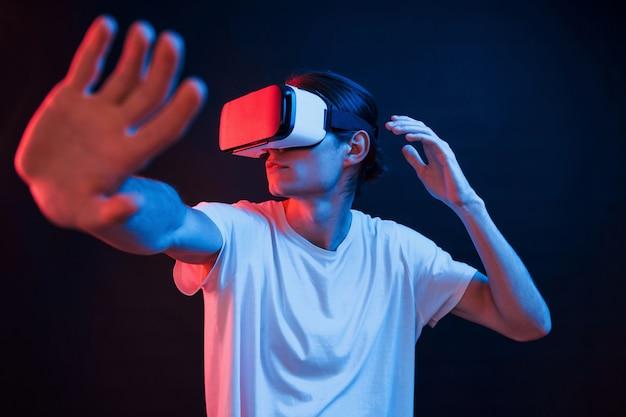 Какая-то аркада. молодой человек в очках виртуальной реальности в темной комнате с неоновым освещением