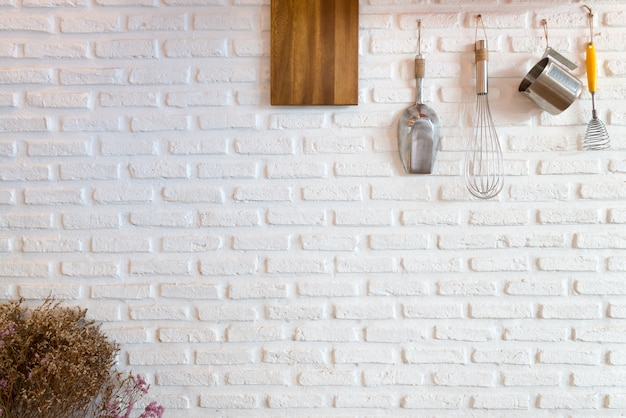 Some kitchenware hang on white brick wall