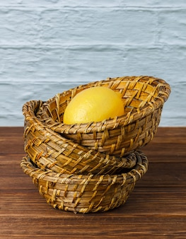木の表面のかごの中のいくつかのレモン、高角度の眺め。テキスト用のスペース
