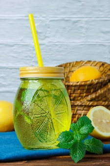 Some lemon juice jar with leaves, white cloth, lemons in basket on wooden and white surface, side view. space for text