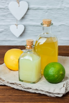 Some lemon and juice with on piece of white cloth in a basket on wooden surface, high angle view.