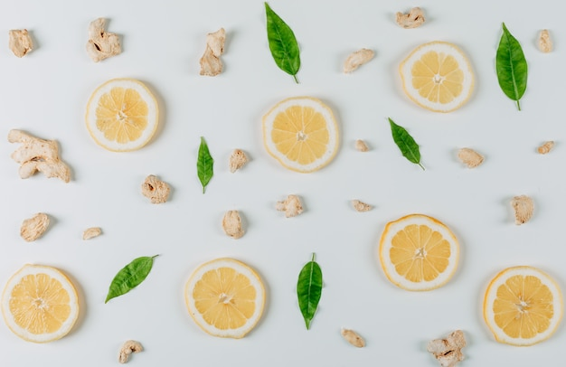 Some lemon slices with ginger and leaves on white background, top view.