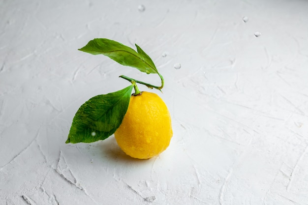 Some lemon with leaves on white textured background, high angle view. space for text