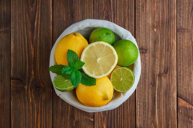 Некоторые лимоны в корзине на деревянной поверхности, вид сверху.