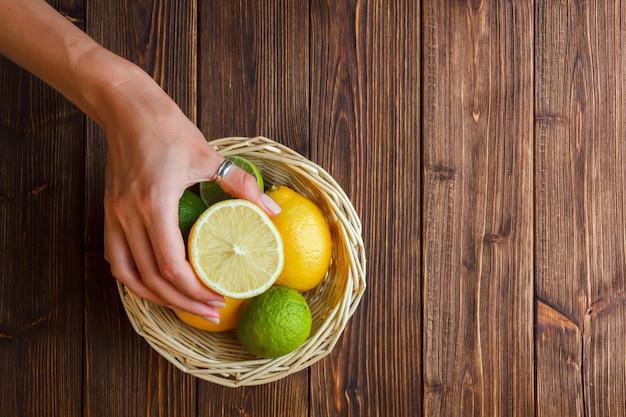 Alcuni limoni con la mano che tiene la metà del limone in un cesto su fondo in legno, vista dall'alto.