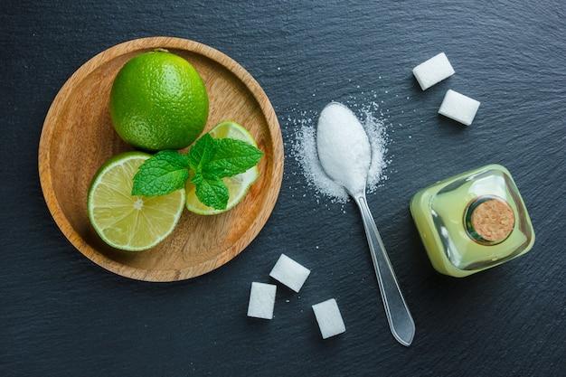 Некоторые лимоны с солью, сахаром, соком в деревянной тарелке на темной каменной поверхности, вид сверху.