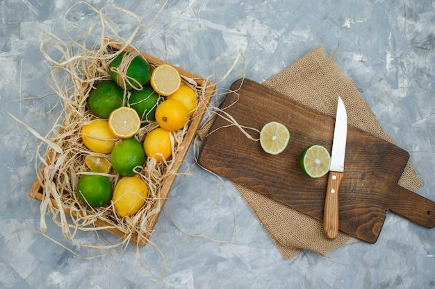 Some limes and lemons with kitchen towel and knife in a cutting board