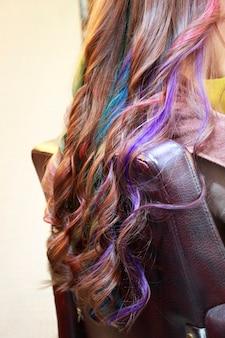 サロンでプロの美容師が設定しながらいくつかの長い色のスパイラルヘア