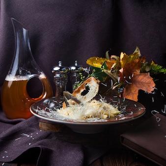 黒の背景、側面図の黒い皿にいくつかのマカロニ。