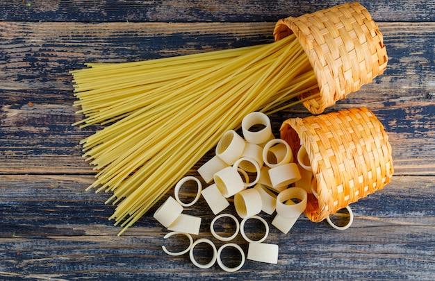 Некоторые макаронные изделия макарон с спагетти в ведрах на темной деревянной предпосылке, взгляд сверху.