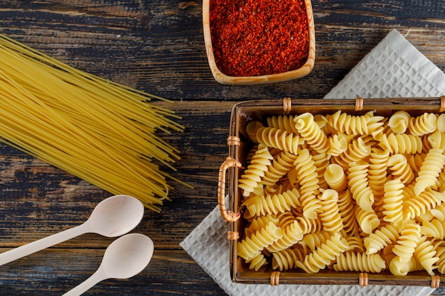 Some macaroni pasta with spaghetti, spoons in a tray on wooden background, top view.
