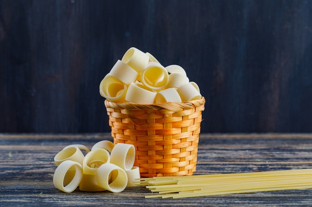 Some macaroni with pasta and spaghetti in a bucket on dark wooden background, side view. space for text