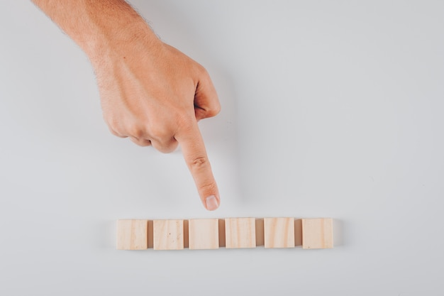 Some man pointing to wooden blocks on white