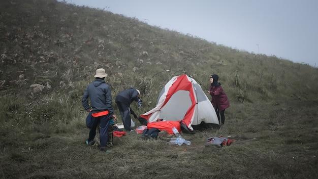 Несколько альпинистов, которые убирают свои палатки, чтобы подготовиться к возвращению домой