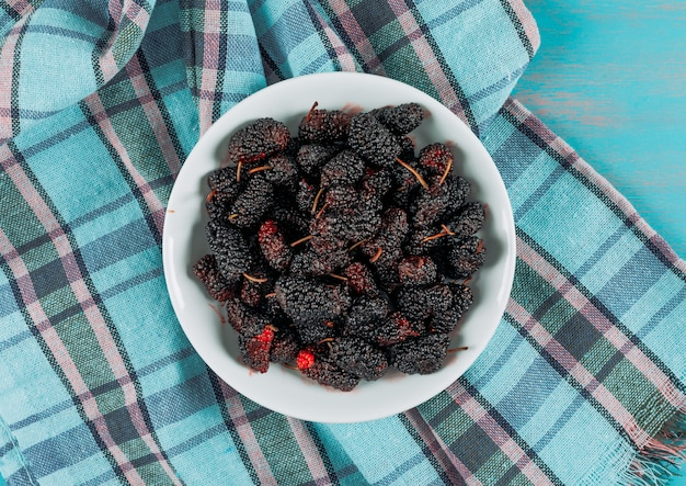 Some mulberries in a plate on picnic cloth and blue wooden background, top view.
