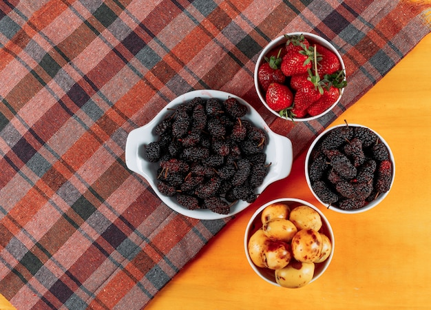 Some mulberries with strawberries, loquats in bowls on cloth and yellow wooden background, top view.