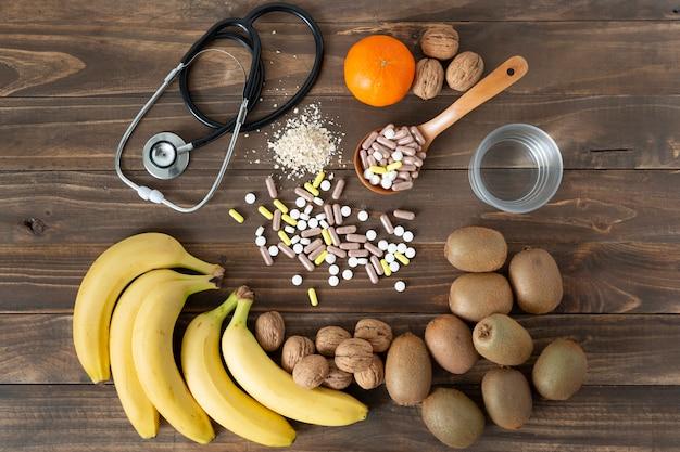 어두운 나무 테이블에 음식을 돌보는 몇 가지 영양소, 과일 및 의약품. 건강한 라이프 스타일 개념.