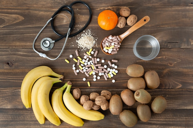 Some nutrients, fruits and medicines to take care of food on a dark wooden table. healthy lifestyle concept.