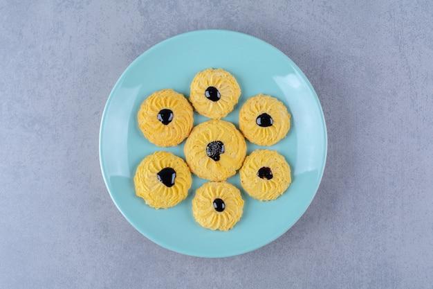 青いプレートにチョコレートシロップが入ったおいしい黄色いクッキーのいくつか。