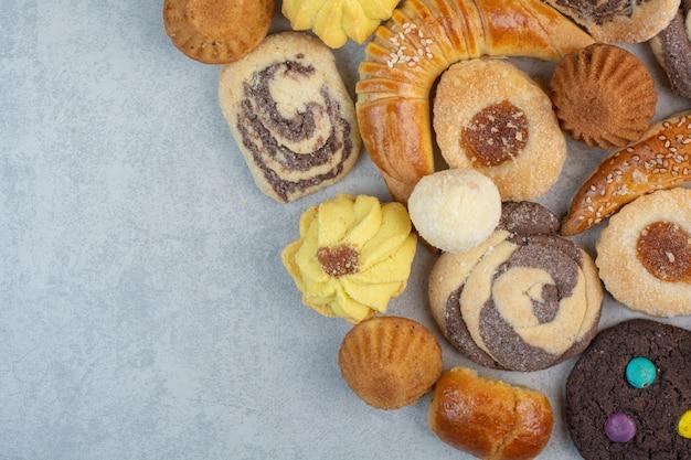 白いテーブルの上の新鮮なおいしいクッキーのいくつか。