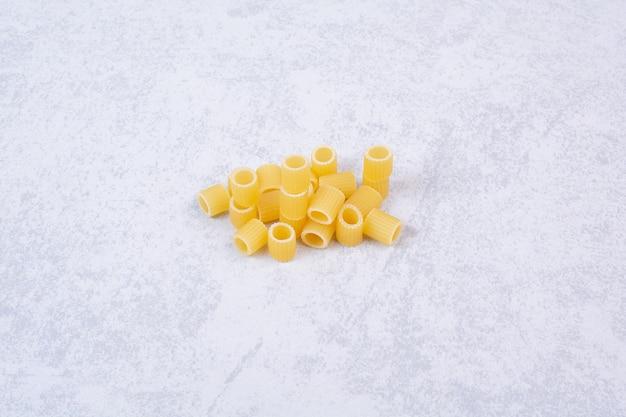 Некоторые из свежих сырых макарон на белой поверхности