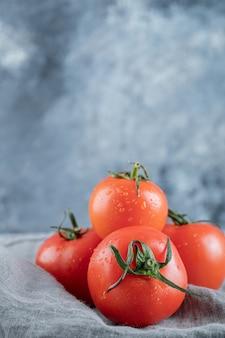 Некоторые из свежих помидоров на серой скатерти.