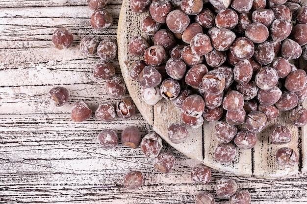 白い木製のテーブルに殻から取り出されたヘーゼルナッツのいくつか