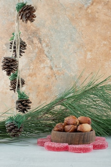 Некоторые из сахарного красного мармелада с деревянной миской, полной сухофруктов на белом фоне. фото высокого качества