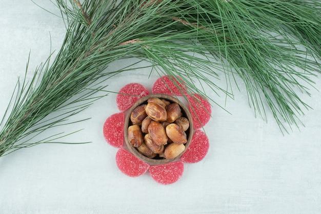 흰색 바탕에 말린 과일의 전체 나무 그릇과 설탕 빨간 마멀레이드의 일부. 고품질 사진