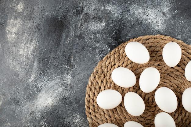 Некоторые белые сырые куриные яйца на вретище.
