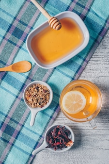 Some orange colored water with honey and tea herbs on picnic cloth and gray wooden background, top view.
