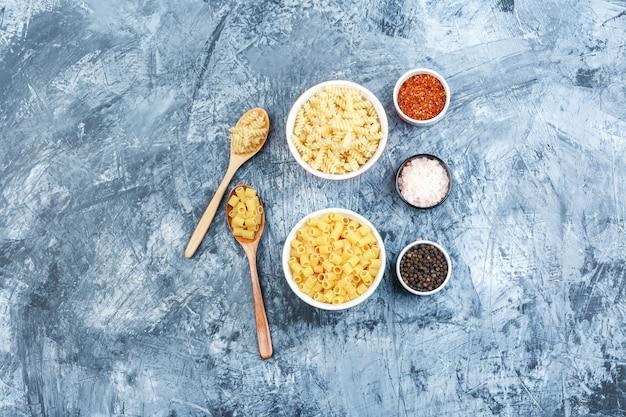 Un po 'di pasta con le spezie in ciotole bianche e cucchiai di legno su uno sfondo di gesso grungy, piatto laici