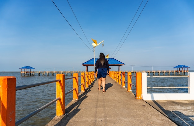 Some people walking on the bridge in the blue sea