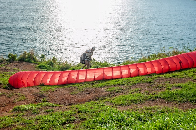 Some people with parachute sport extreme on island sunset in twilight