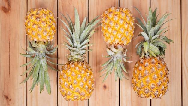 木製の背景にいくつかのパイナップル