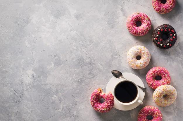 灰色の石のテクスチャ、上面図、コピースペースの上にコーヒーのカップといくつかのピンクと白のドーナツ