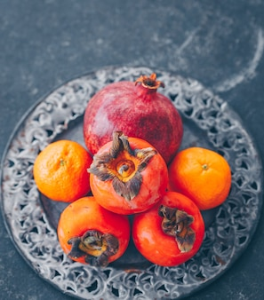 Some pomegranate and persimmon with mandarin in metal plate on dark, high angle view.