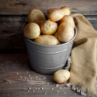 Some potatoes in a gray bucket on dark wooden background, high angle view.