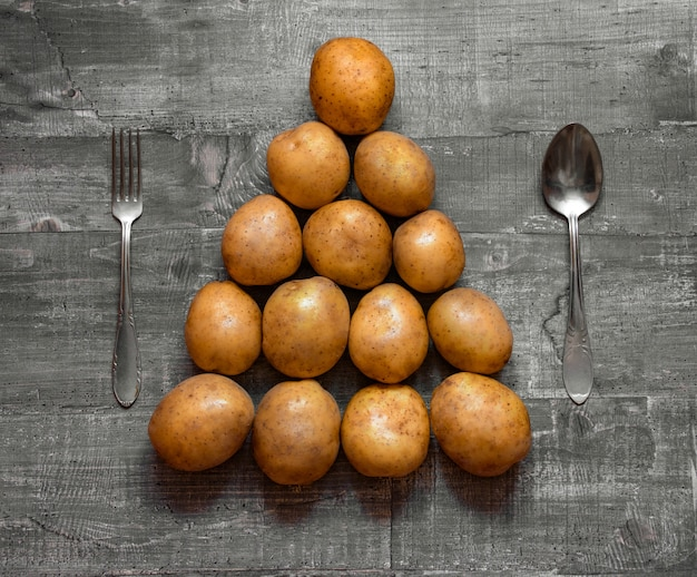 Some potatoes on an old wooden table or wooden surface is laid out in the shape of a christmas tree. layout top view