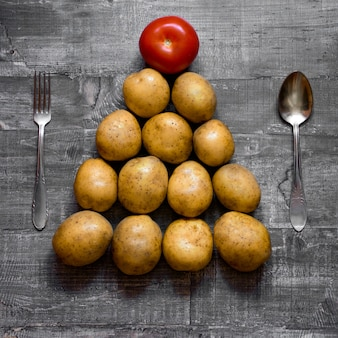 Some potatoes and a tomato on an old wooden table or wooden surface is laid out in the shape of a christmas tree. layout top view
