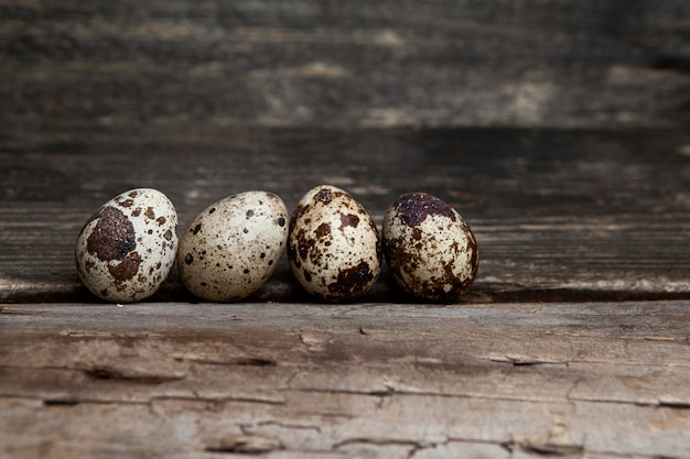 Some quail eggs on dark wooden background, side view. free space for your text