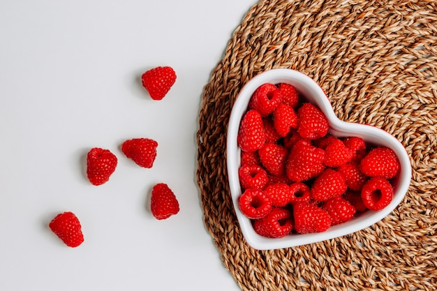 Some raspberries in a heart shaped bowl on trivet and white background, top view.