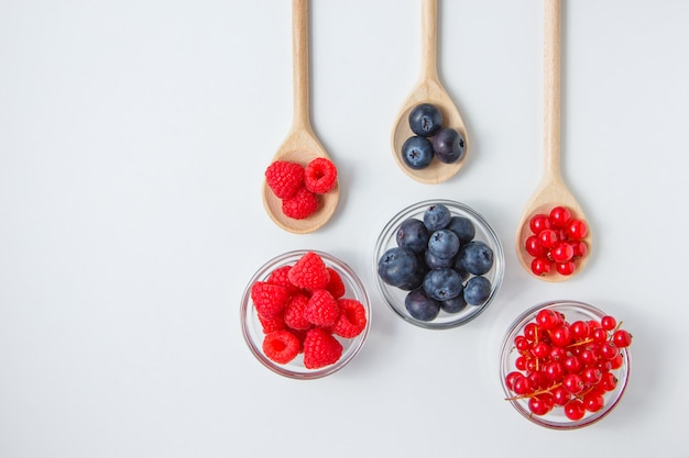 Some raspberries with blueberries in a spoons and saucers, top view.