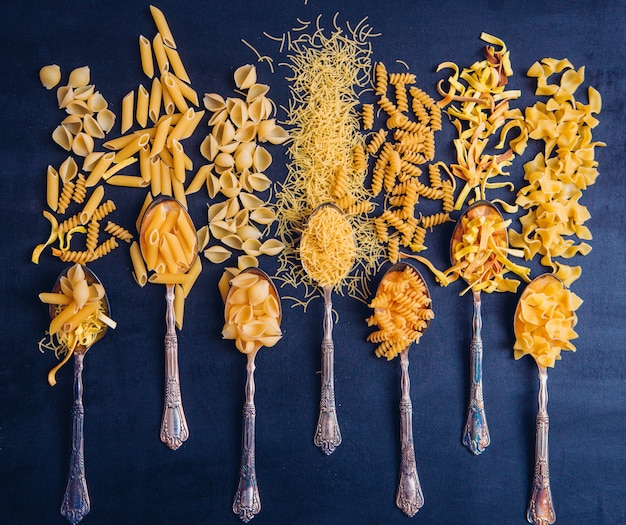 Some of ready cut macaroni on 7 spoons and around